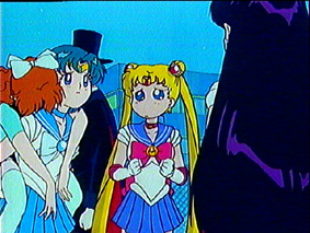 A screen capture of Sailormercury with Naru on her back, the back of Sailormars, Sailormoon looking bewildered, and Tuxedo Kamen hidden in the background
